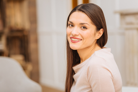 Natural posing. Nice beautiful vigorous woman listening to someone while looking straight and smiling Stock Photo