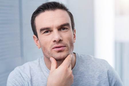 Man bristles. Tranquil attentive reliable man looking straight and examining his bristles while staring at the camera