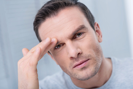 Horrible headache. Young pensive sad man experiencing headache so needs pills while touching his head