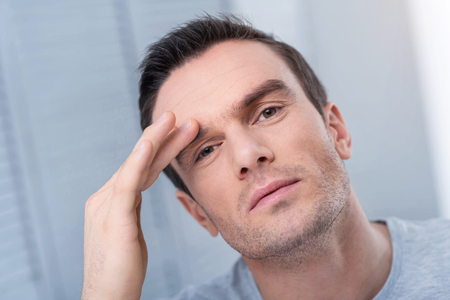 Day planning. Pensive young concentrated man planning his daily routine  while placing hand on his forehead and looking straight Stock Photo