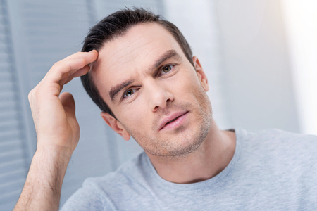 Strange situation. Confused pensive serious man hearing unexpected news  while gazing at the camera and touching his forehead Stock Photo