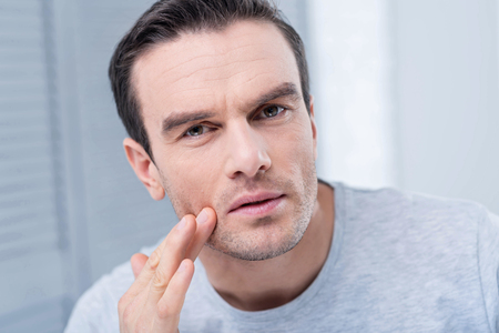 Strange rush. Concerned earnest unhappy man looking at the camera and scrutinizing his face while touching face with a finger Stock Photo