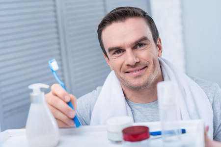 Smoothy skin. Gay young positive man shaving his beard while looking at the mirror and touching face