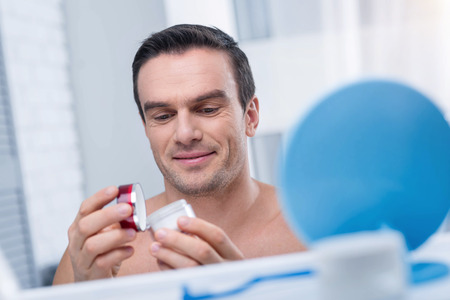 Face cream. Happy cheerful gay man closing cream container white looking down and smiling