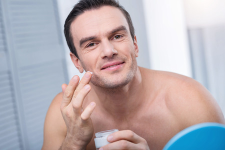 Obligatory minerals. Attractive young brunette man has face cream on a finger while gazing at the camera  and posing against blurred background