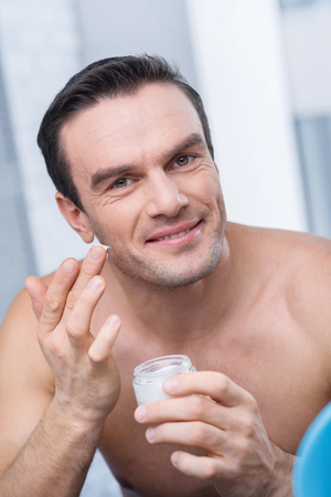 Appropriate cream. Pleasant confident tranquil man putting cream on his face while grinning and staring at the camera