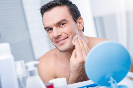 Clean face. Attractive positive cute man wiping his skin with disc while smiling at the camera and standing against blurred background