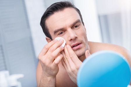 Cleaning procedure. Good looking young thoughtful man staring at the mirror and examining his face while cleaning it Stock Photo