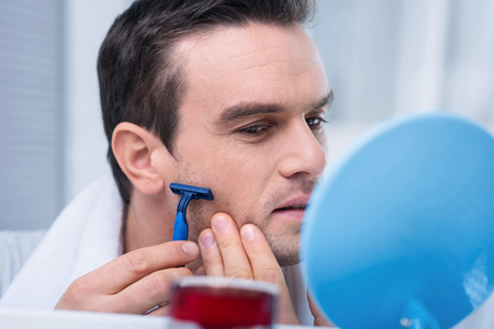 Last touch. Fascinating appealing brunette man holding razor while shaving his neck  and supporting it with a hand