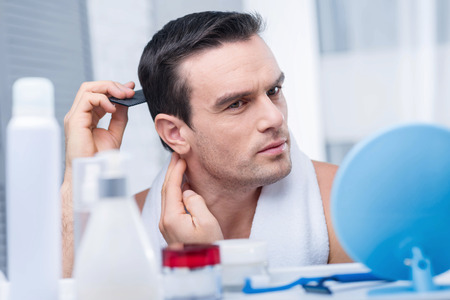 Hair style. Attractive pleasant nice man combing hair while looking in the mirror and posing on the blurred background