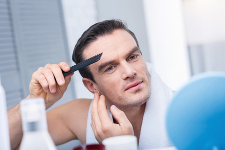 Ideal hear cut. Tranquil happy young man enjoying morning while staring at the mirror and holding comb