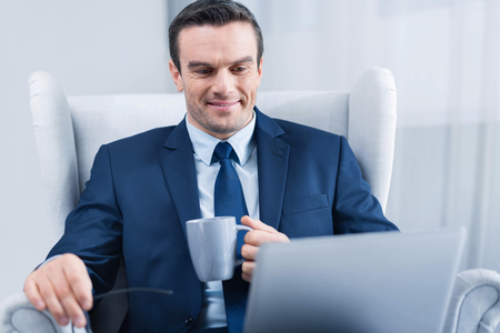 Routine work. Attractive nice young man  sitting in the armchair and drinking tea while looking at the screen