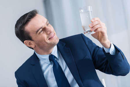 Life in water. Joyful pleasant attractive man smiling while  staring at the glass of water and holding it