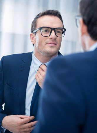 Ideal look. Pretty cute happy man touching his tie while staring at the mirror and wearing glasses