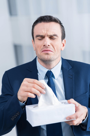 Season cold. Strong good looking young man holding tissue while  preparing to sneeze