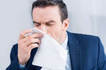 Capricious cold. Handsome brunette tired man  bringing tissue to the nose while closing his eyes and posing on the white background