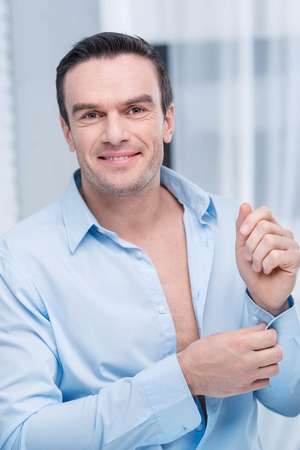 Dressing for work. Attractive young merry man dressing and wants to go at work  while posing on the blurred background