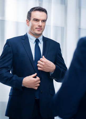 Moral challenge. Irresistible handsome young man touching jacket while standing right and preparing morally Stock Photo
