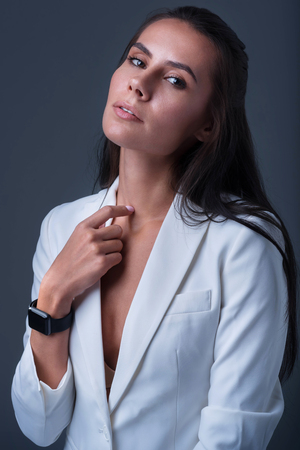 Business flirt. Attractive impressive pensive woman wearing smart watch and touching her neck with a finger while gazing at the camera Stock Photo