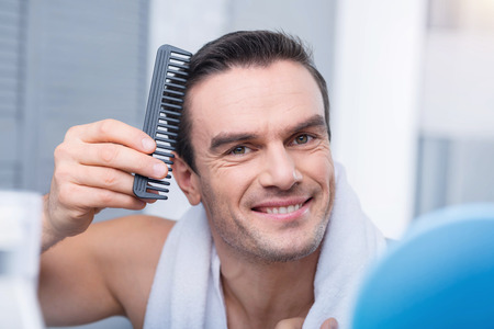 Perfect hair cut. Pleasant gorgeous cheerful man combing hair  smiling to the camera and standing against the blurred background