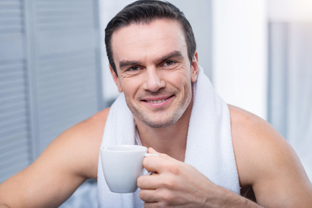 Morning coffee. Joyful marry appealing man enjoying coffee and holding cup while looking straight