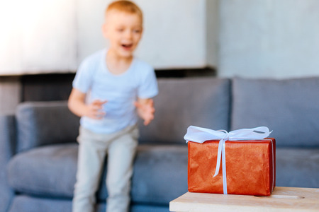 Wonderful surprise. Selective focus of a red present box standing on the table with a happy excited kid standing in the background Stock Photo