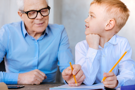 Early development. Nice smart delighted boy holding a pencil and taking notes while studying together with his grandfather Stock Photo