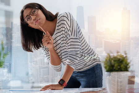 Let me think. Clever young woman leaning on table and holding pencil near chin while making plan