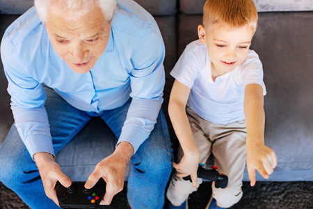 Time with family. Nice positive elderly man sitting together with his grandson and holding a game console while playing video games with him