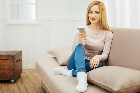 Watching TV. Beautiful smiling young slim blond woman holding a remote control and wearing jeans and a beige sweater and warm socks and sitting on the couch with cushions in the room