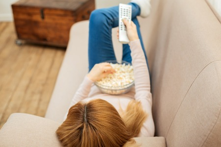Leisure time. Blond young long-haired woman using a remote control while eating popcorn and lying on the sofa in jeans and a sweater