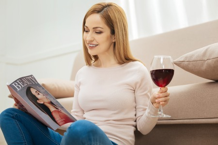 Woman of fashion. Pretty happy blond long-haired woman smiling and holding a glass of red wine and looking through a fashion magazine while sitting on the floor near the sofa