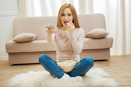 Watching films. Attractive inspired young blond woman holding a remote control and eating popcorn while sitting on the floor near the couch Banco de Imagens