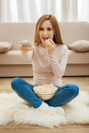 Watching TV. Attractive inspired young blond woman holding a remote control and eating popcorn while sitting on the carpet on the floor near the couch