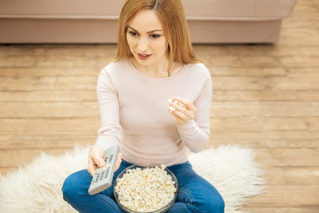 Choosing a film. Good-looking concentrated young blond dark-eyed woman holding a remote control and eating popcorn while sitting on the carpet on the floor near the couch