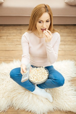 Great weekend. Good-looking cheerful young blond dark-eyed woman holding a remote control and eating popcorn while sitting on the carpet on the floor near the couch Banco de Imagens