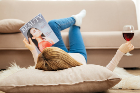 Fashionable woman. Blond slim long-haired woman holding a glass of red wine and looking through a fashion magazine while lying on the carpet on the floor near the sofa