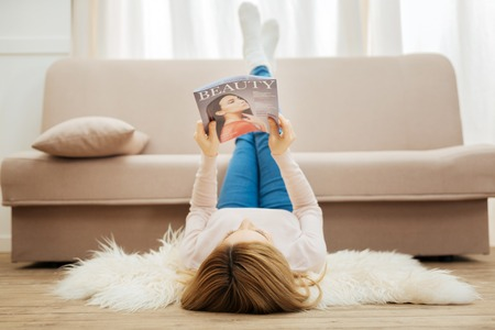 Fashion magazine. Blond long-haired slim woman holding a fashion magazine and having her feet up while lying on the carpet on the floor near the sofa and wearing jeans and a sweater Stock Photo