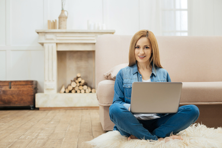 Freelancing. Good-looking content blond young woman smiling and sitting with her laptop on the floor near the sofa and wearing jeans and a jacket and a fireplace in the background