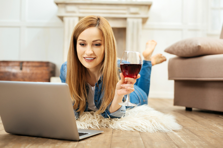 Great time. Beautiful dark-eyed blond smiling woman lying on the floor and holding a glass of red wine and working on her laptop Stock Photo