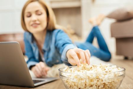 Me encantan las palomitas de maíz. Hermosa rubia sonriente mujer de pelo largo acostado en la alfombra y comiendo palomitas mientras trabajaba en su portátil Foto de archivo