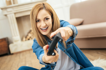 Avid player. Alert blond young dark-eyed woman smiling and playing a game while sitting on the floor and wearing a jeans costume Stock Photo