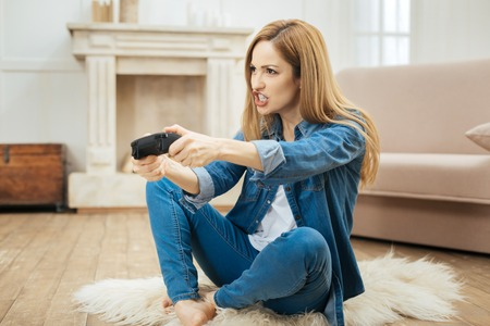 Having fun. Beautiful determined blond young woman smiling and playing a game while sitting on the carpet on the floor and wearing a jeans costume Stock Photo