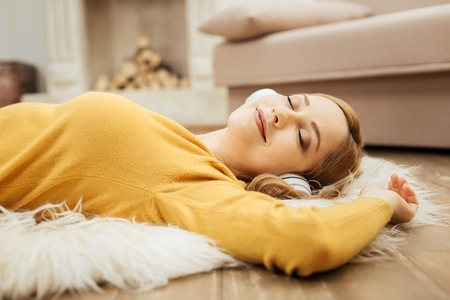 Feeling great. Beautiful content young blond woman smiling and listening to music and wearing headphones while lying on the floor with her eyes closed and wearing a yellow sweater