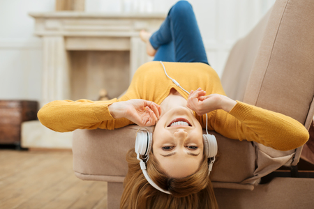 On cloud nine. Pretty alert young blond woman smiling and listening to music and wearing headphones while lying on the sofa and wearing a yellow sweater and a fireplace in the background