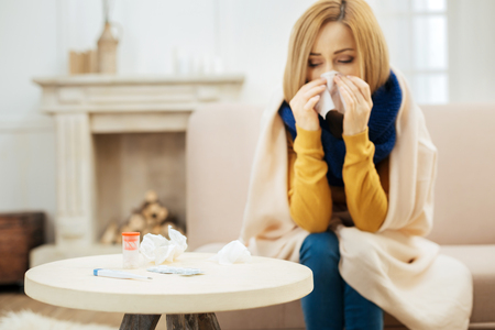 Feeling ill. Ill young blond woman feeling bad and blowing her nose while having a blanket on her shoulders and sitting on the couch and table with pills in front of her