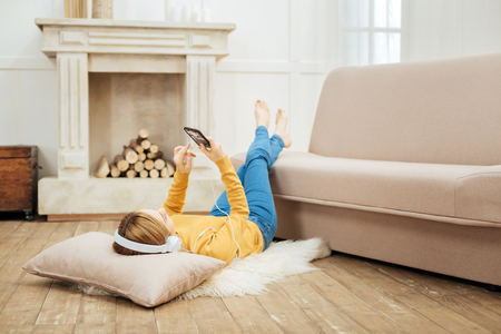 Weekend. Young blond slim woman listening to music and wearing headphones and holding her phone while lying on the floor and a cushion under her head and a fireplace in the background Stock Photo