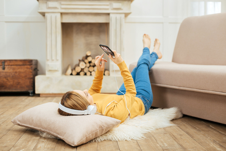Having holidays. Young blond slim woman listening to music and wearing headphones and holding her phone while lying on the floor and a cushion under her head and a fireplace in the background