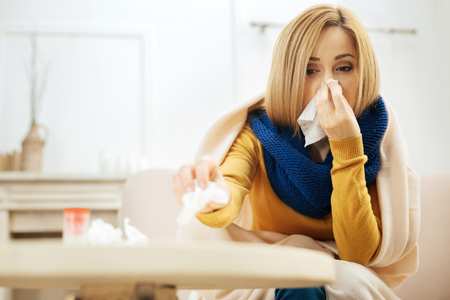 Blocked nose. Ill young blond woman blowing her nose while having a blanket on her shoulders while sitting on the couch and putting used napkins on the table in front of her