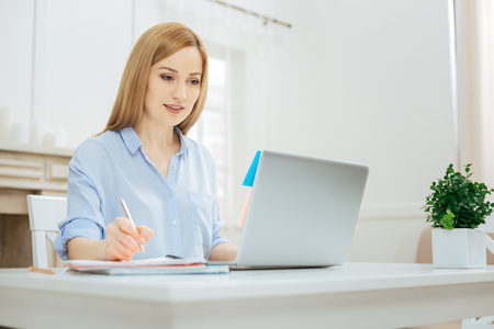 Project. Pretty smiling young blond woman wearing a shirt and writing something down while sitting at the table and working on her laptop and a flower on her table